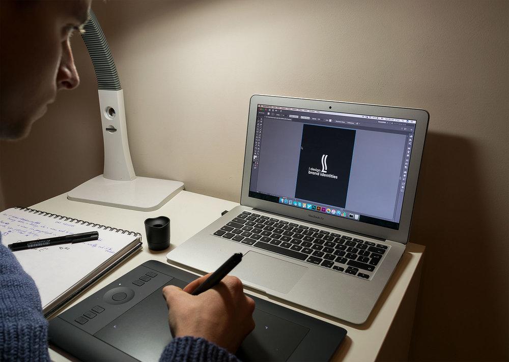 lukas-graphic-design-sitkus-macbook-designer-illustrator-photoshop-desk-work-job-wacom-tablet-pen-paper-sketch-notebook-lamp