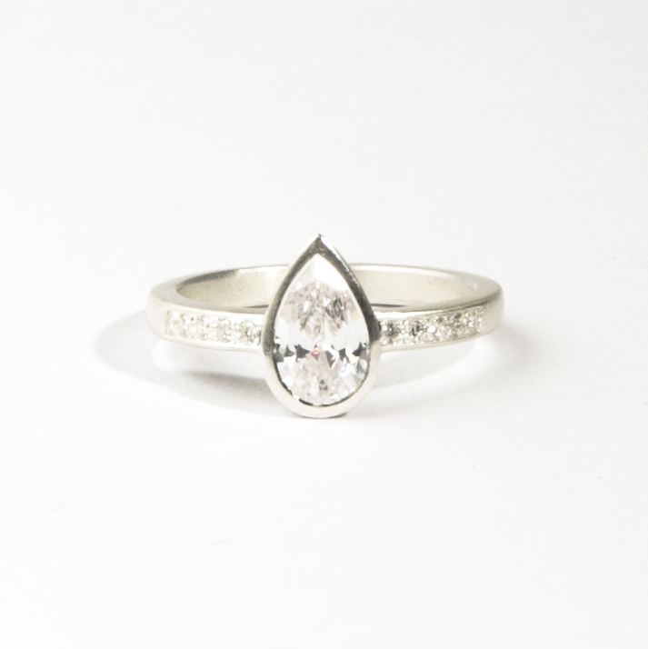 18ct white gold pear shaped diamond ring, set with grain set diamond shoulders.