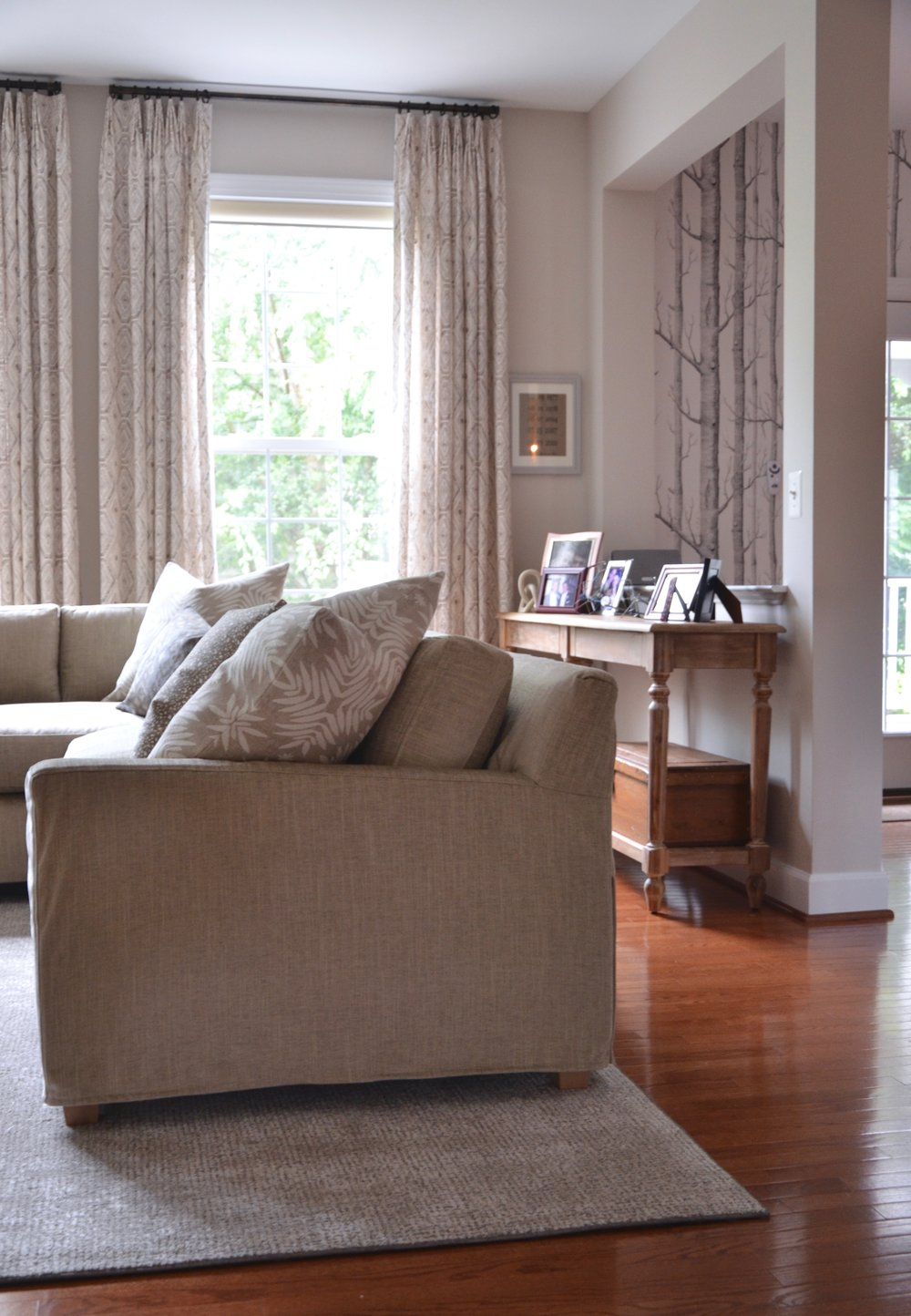 After:no more builder basic. Now a custom sectional, rug, and window treatments have wholly upgraded this family room in Herndon, VA.