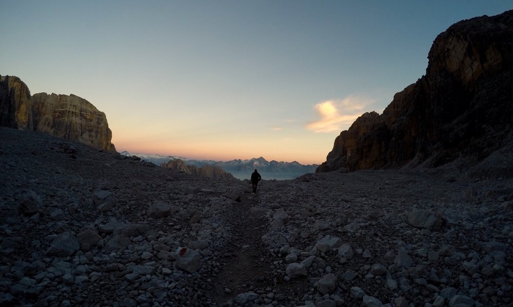 Young man walks off into the distance in the Brenta Dolomites at sunset