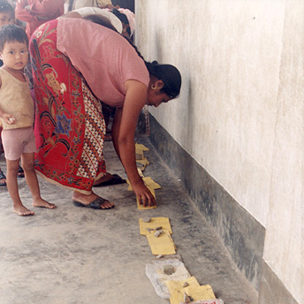 A woman is putting her child's health care card in line to see the Health Assistant.  It takes around two hours of waiting to get a patient check up.   The service in the camps is not so good.   Ram  / PhotoVoice / LWF