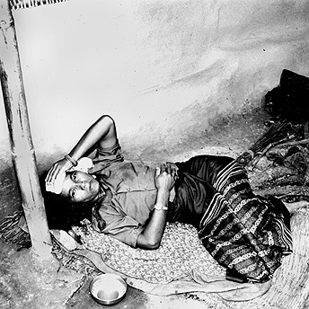An ill woman lies outside her hut.  Many people get sick in the summer season because it is so hot in the camps.  Bishnu Maya  / PhotoVoice / LWF