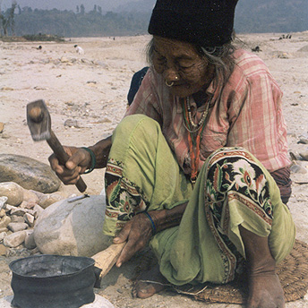 A old woman is breaking stones with a hammer. The food items given in rations are not nutritious enough and we are not given clothes.  People do this work in order to earn money to buy extra vegetables and some clothes. Tila Maya / PhotoVoice / LWF