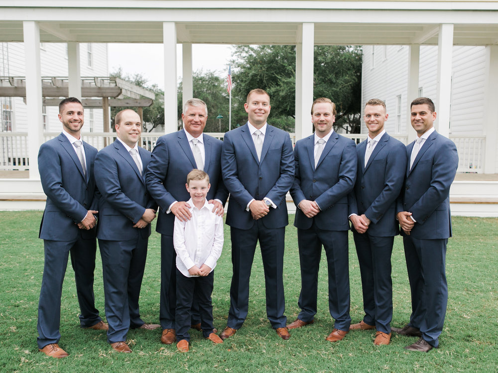 Groomsmen in navy suits with light gray ties