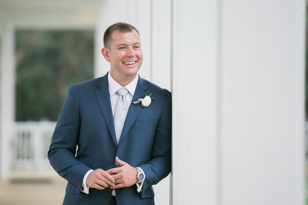 Handsome groom in navy suit with gray tie