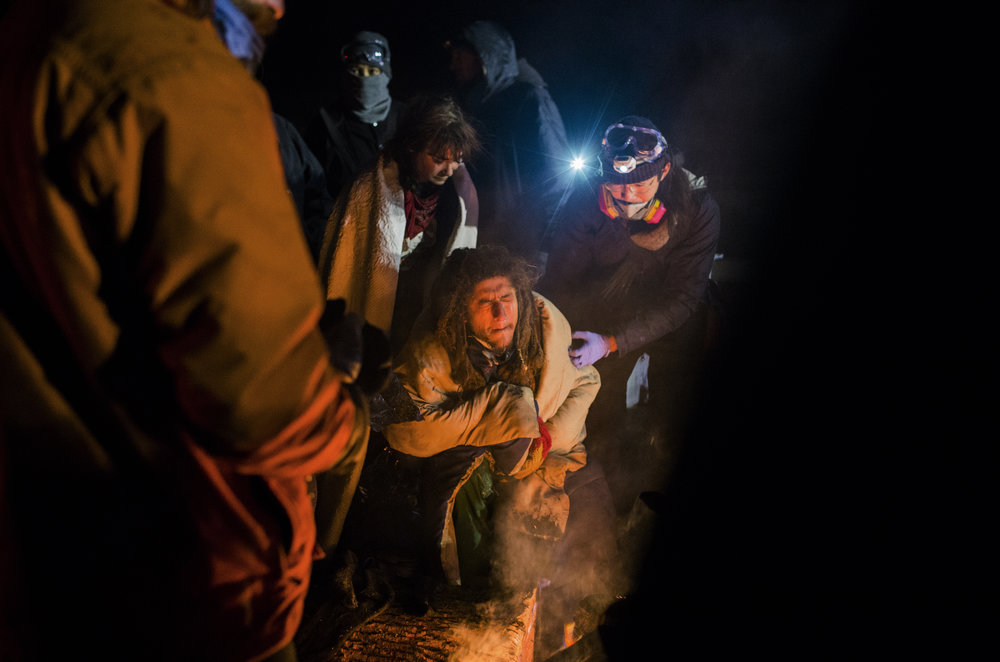 A water protector warms up near a fire after being sprayed with water cannons on the front lines on Sunday, November 20, 2016