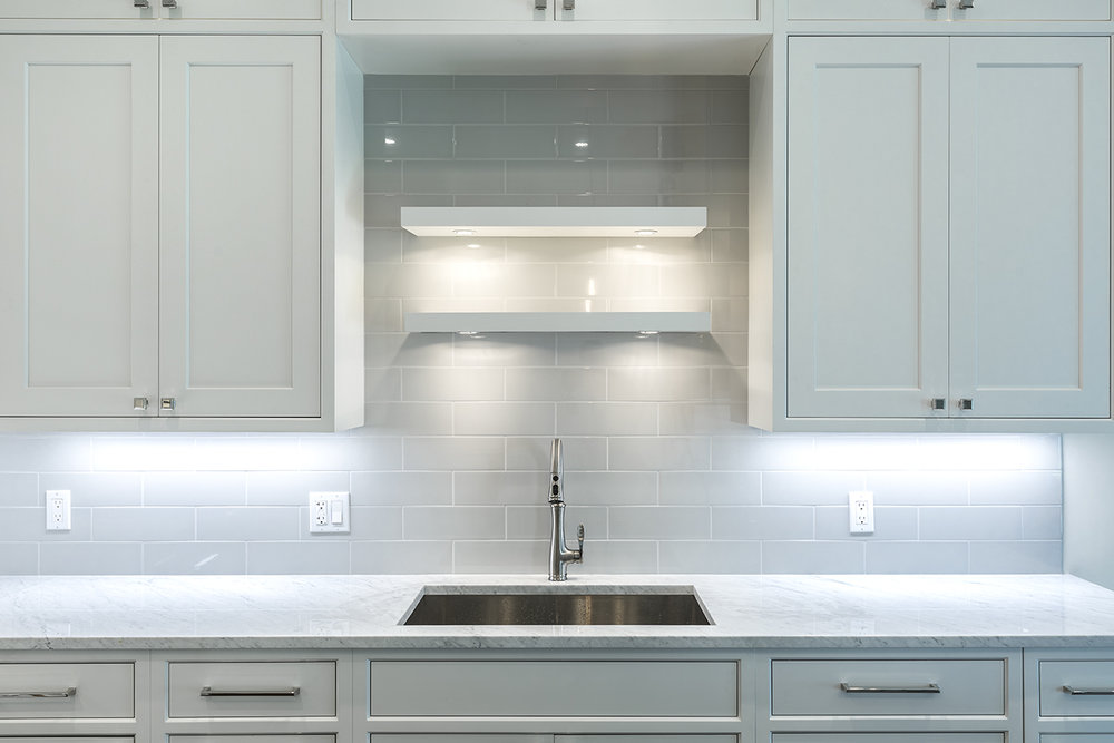 Transitional inset white kitchen with lighted floating shelves
