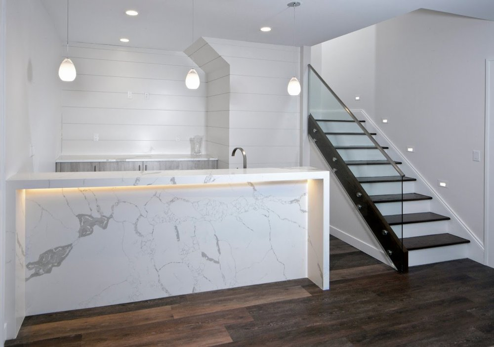 2-bar-basement-led-lit-waterfall-countertop-glass-stair.jpg