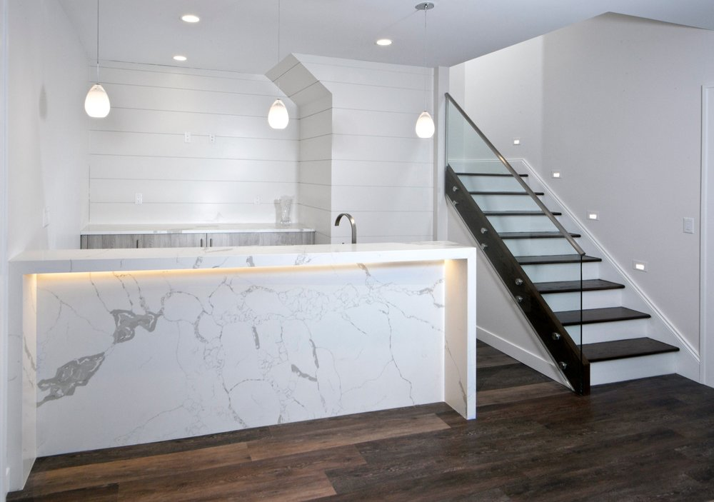 A WET BAR WITH WATERFALL COUNTERTOP AND LED LIGHTING, SHIP-LAP PANELS, AND OPEN STAIR WITH GLASS RAILING AND STEP LIGHTS WAS ADDED.
