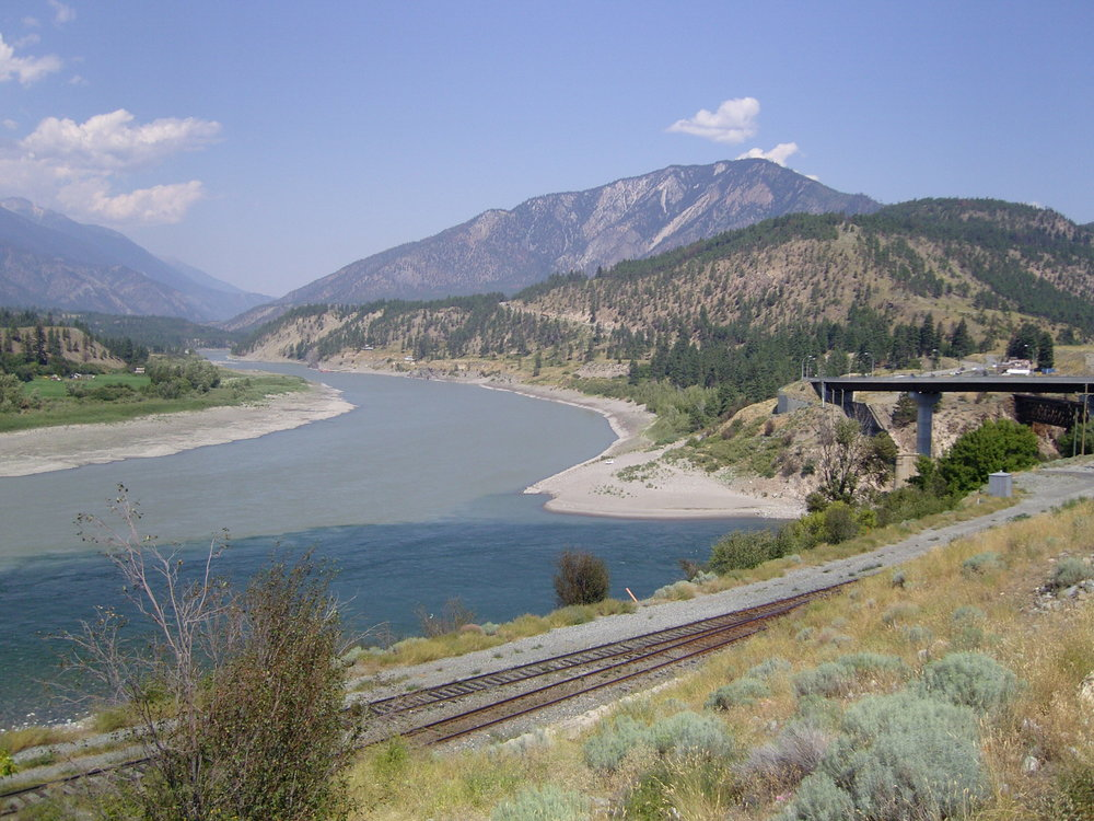 Two rivers meeting is known as confluence. The confluence shows a more turbid, or sediment saturated river (top - Thompson) meeting a more bluish-green river (below - Fraser). Lytton, British Columbia in Canada.  Author Cash4Alex of Creative Commons