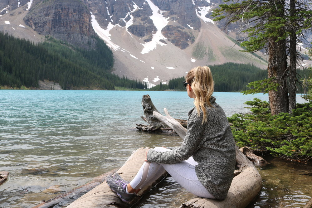 Woman sitting on driftwood at Lake Moraine looking to the mountains