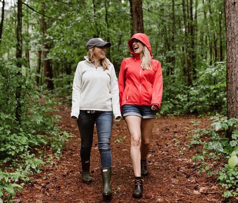 Two woman hiking in the woods laughing