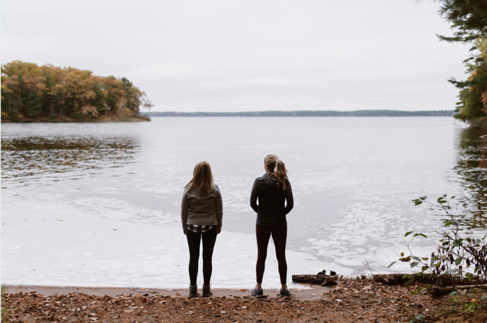 Two woman looking to the horizon from the shore of a northern Wisconsin lake