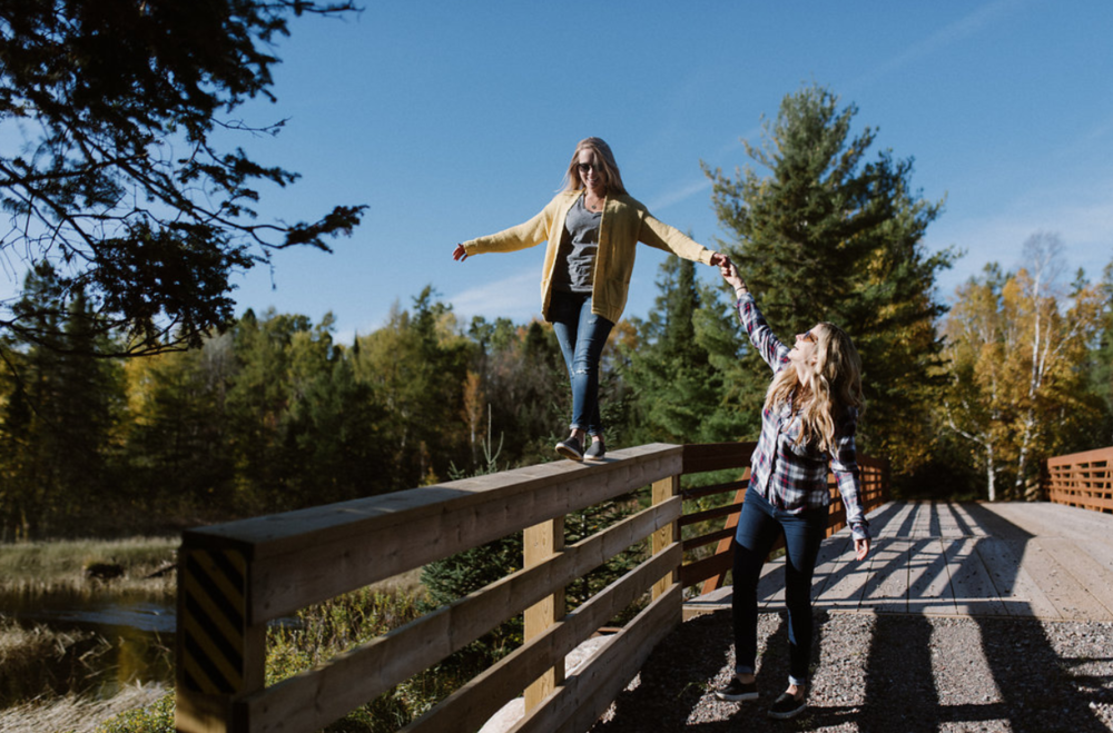 Two woman walking over bridge in northern Wisconsin balancing on top of the railing