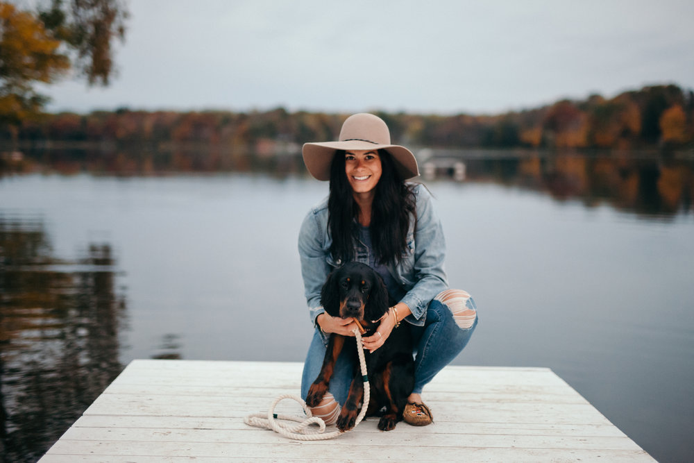 Woman with dog on a pier of a lake