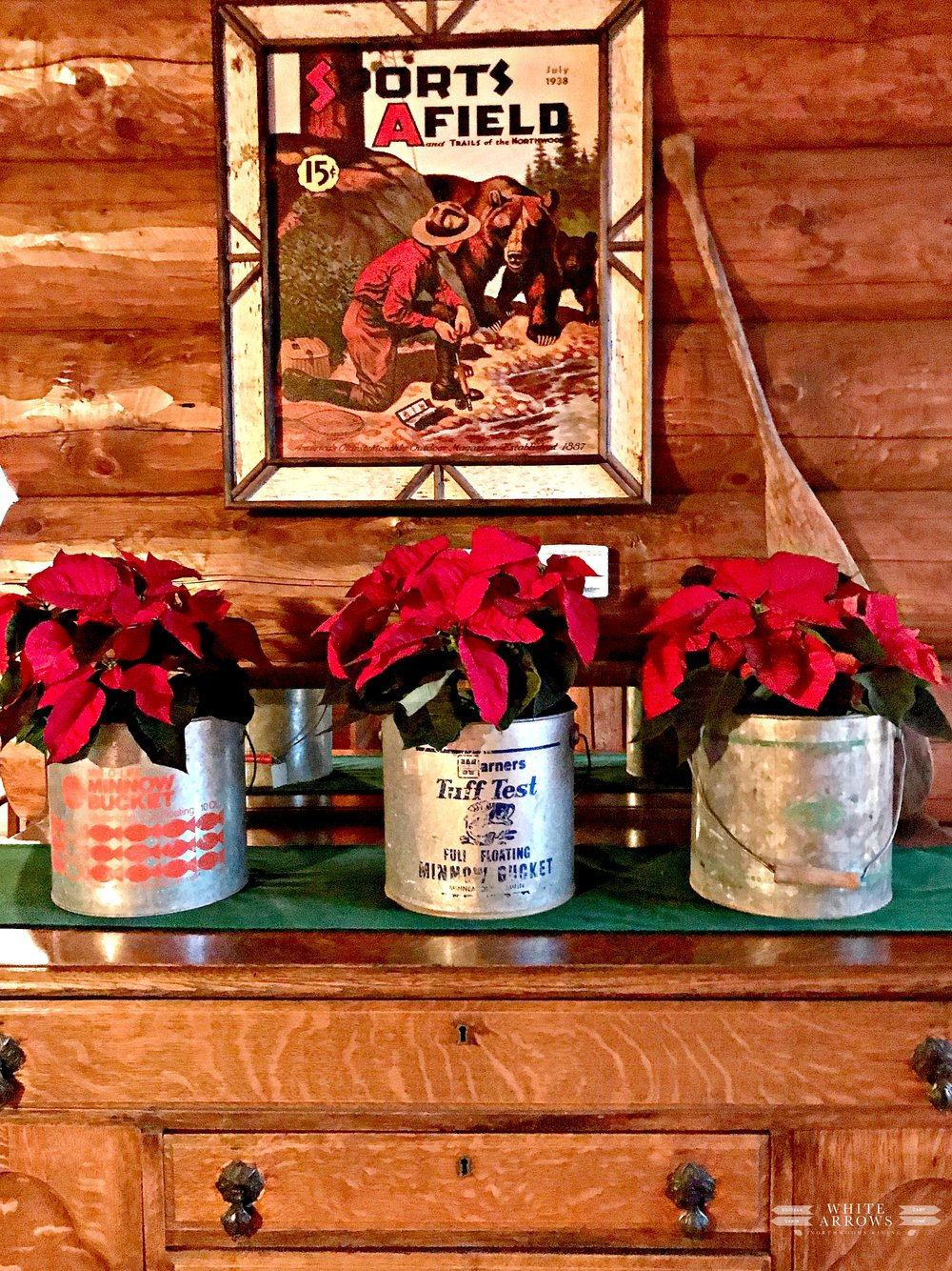 Old minnow buckets repurposed for poinsetta vases in a wooden cabin decoration
