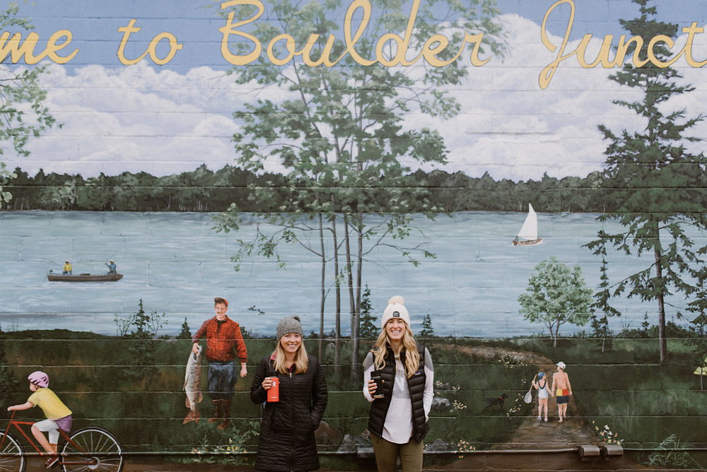 Two women standing in front of a large Welcome To Boulder Junction wisconsin mural
