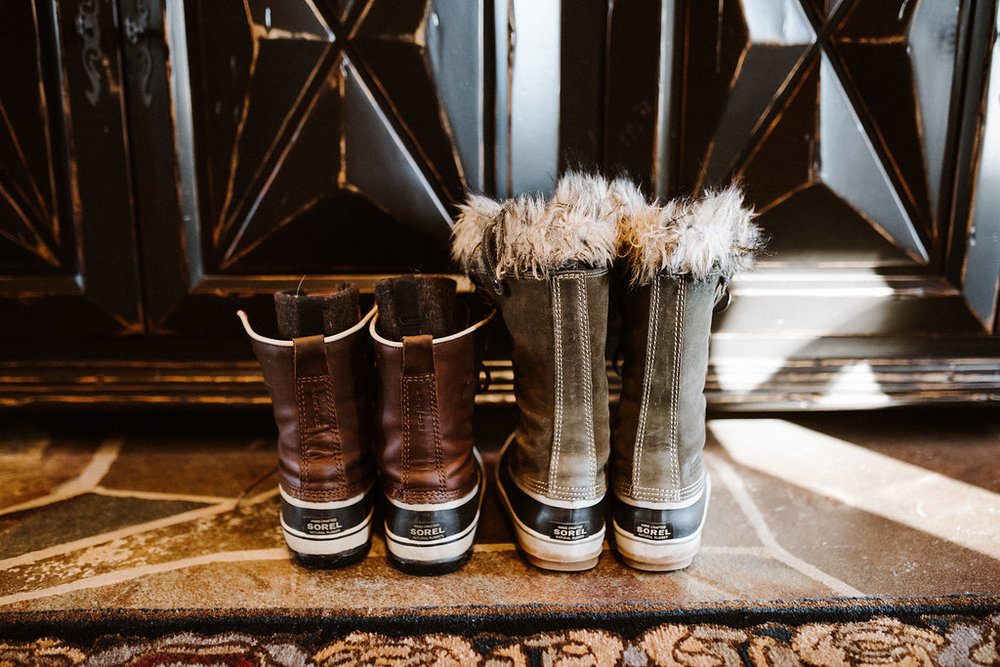 Two pairs of winter boots in front of a fireplace