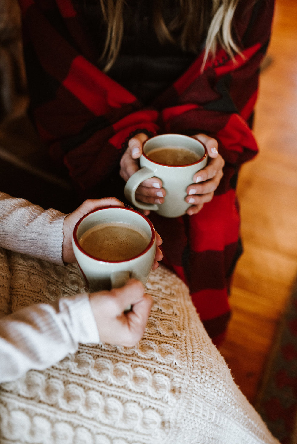 Two women sharing a cozy cup of hot chocolate indoors