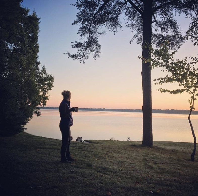 Woman drinking tea watching the sunset in northern wisconsin presque isle at sunrise resort