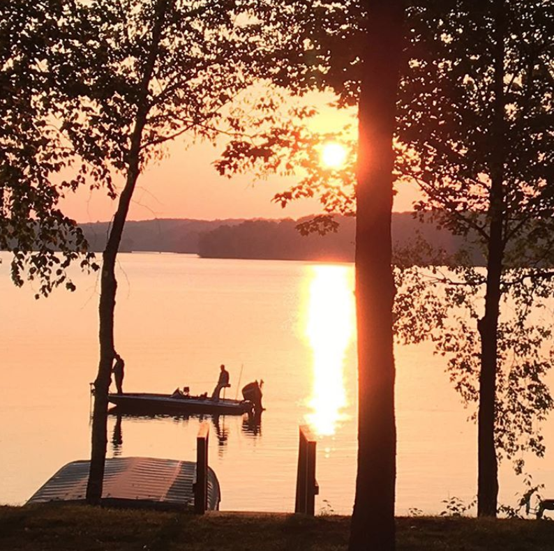 Warm sunset over northern wisconsin lake presque isle with two fisherman in a boat just off the shore