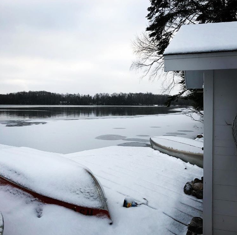 snow covered winter boat house and canoes in northern wisconsin presque isle