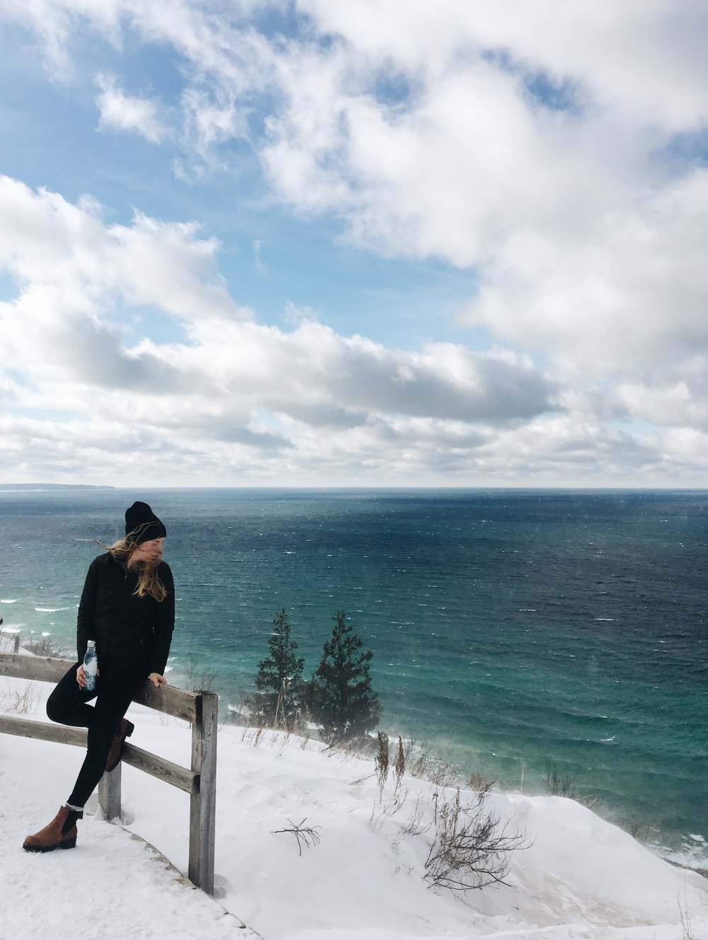 Woman leaning on fence overlooking lake michigan in winter