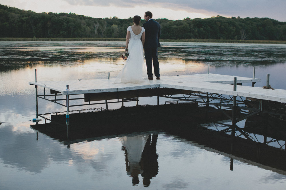 married couple overlooking wisconsin lake on a pier
