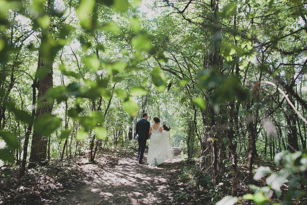 bride and groom walking through woods at camp wandawega