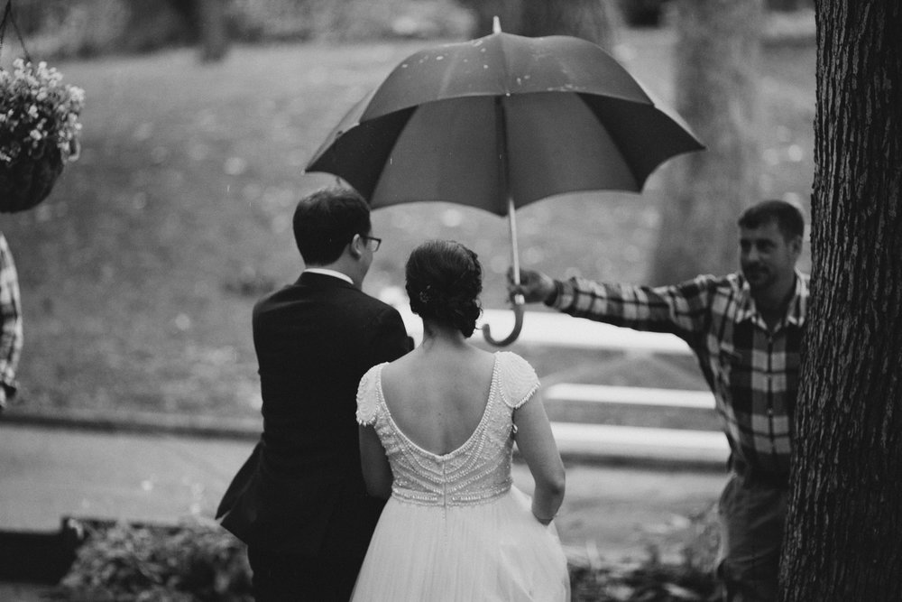 umbrella over bride and groom during outdoor lake wedding