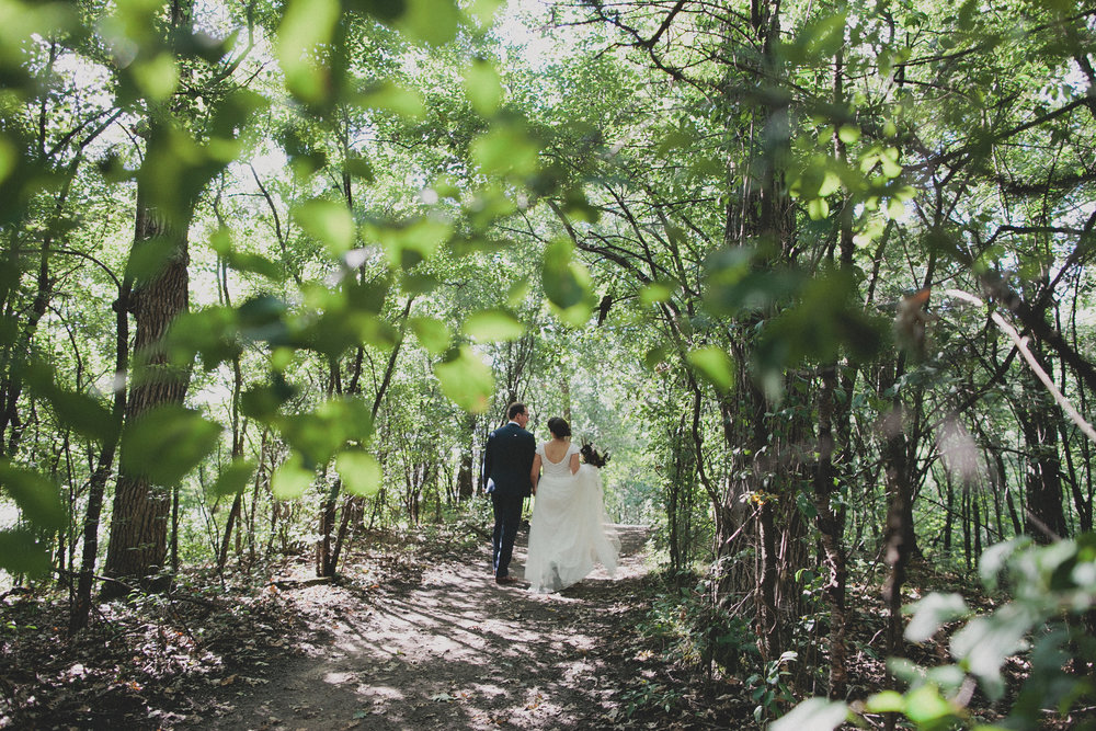 Bride and groom walking in the woods during the summer in Southeast Wisconsin