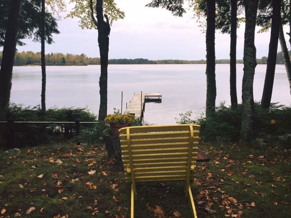 yellow chair overlooking squaw lake in the northwoods wisconsin