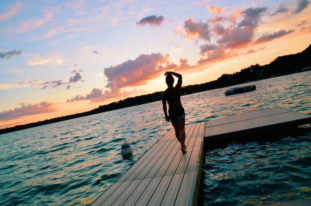 girl walking on pier at sunset