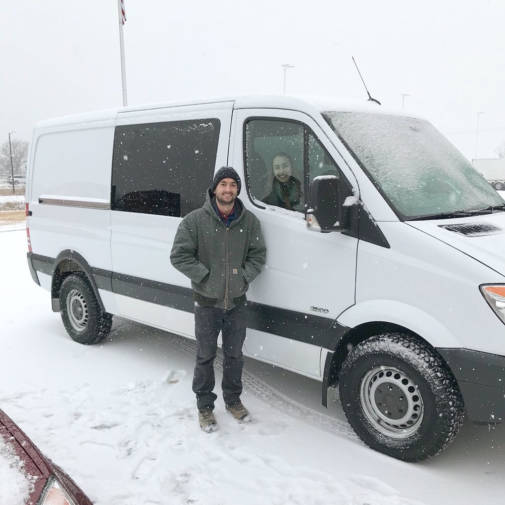 couple standing in front of sprinter van in the snow winter