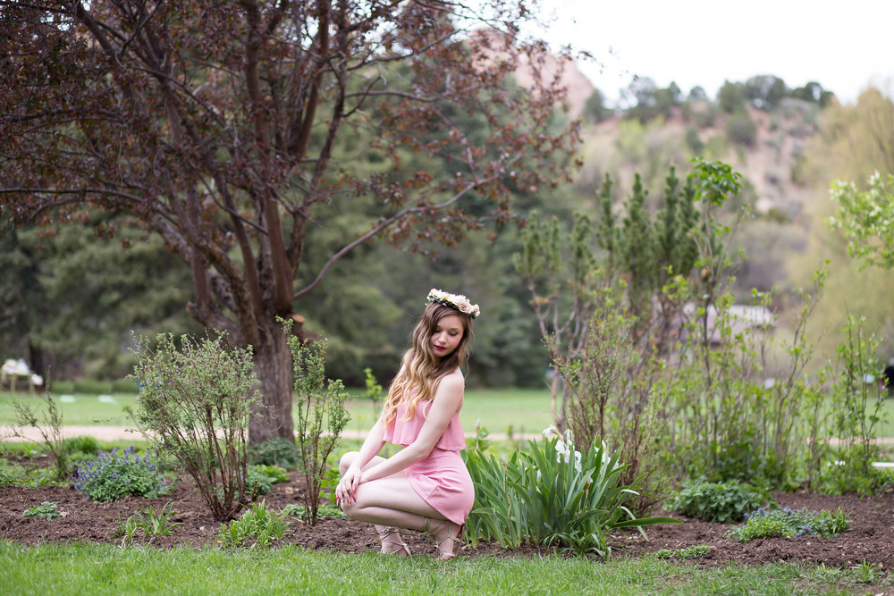 Senior girl kneeling around tall grasses for her senior session at Rock Ledge Ranch in Colorado Springs, CO with floral crown and pink jumper Stacy Carosa Photography