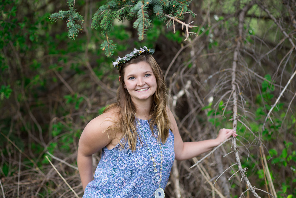 Senior girl smiling at the camera wearing a floral crown while at Rock Ledge Ranch. Stacy Carosa Photography Colorado Springs Senior Portraits Denver Senior Portraits