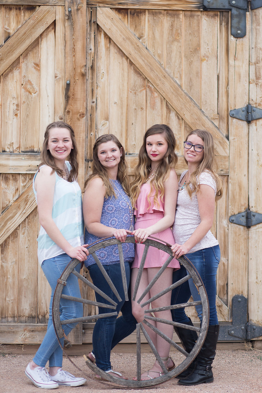 Four senior girls standing next to each other holding a wagon  wheel in front of barn door at Rock Ledge Ranch Stacy Carosa Photography Colorado Springs Senior Portraits