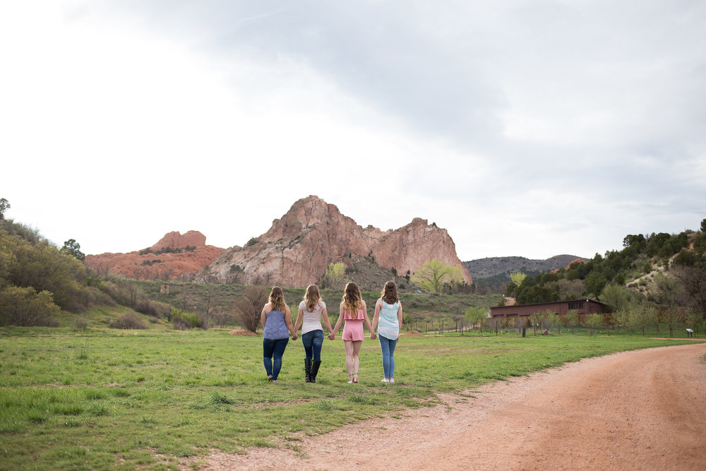 Four friends holding hands and walking toward the red rocks of Garden of the Gods in the distance while at Rock Ledge Ranch for senior photos. Stacy Carosa Photography Colorado Springs