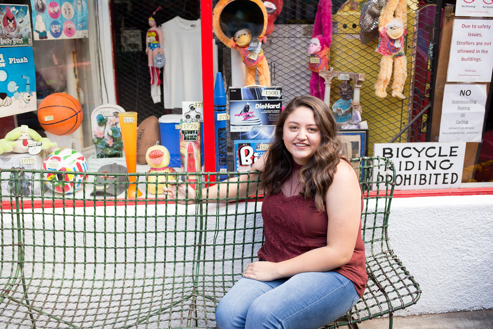 Senior girl sitting on wit bench with toys displayed in store window Photos Manitou Springs Liberty High School Colorado Stacy Carosa Photography
