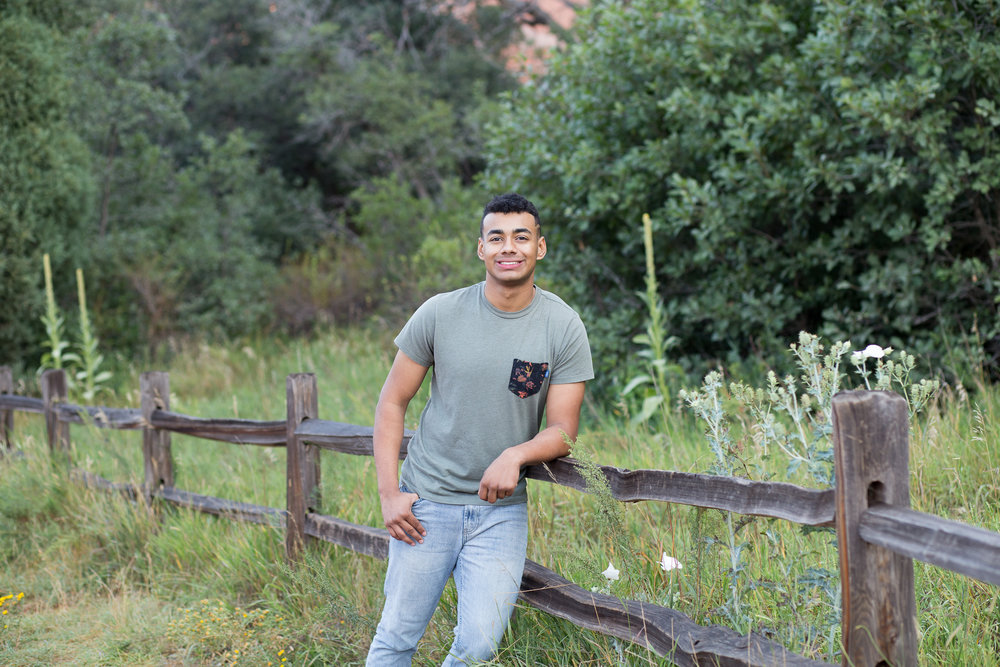 Liberty High  School senior boy leaning on fence in Garden of the Gods park for senior photos, Stacy Carosa Photography
