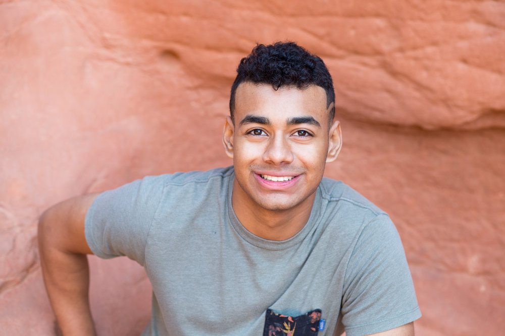 Liberty High School senior smiling at the camera in Garden of the Gods  among the red rocks,  Stacy Carosa Photography, Colorado Springs seniors