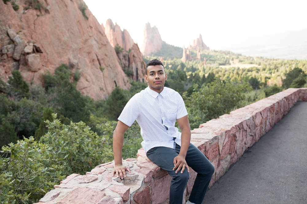 Colorado Springs male senior portraits at Garden of the Gods leaning on rock wall with Garden of the Gods in the background, Stacy Carosa Photography