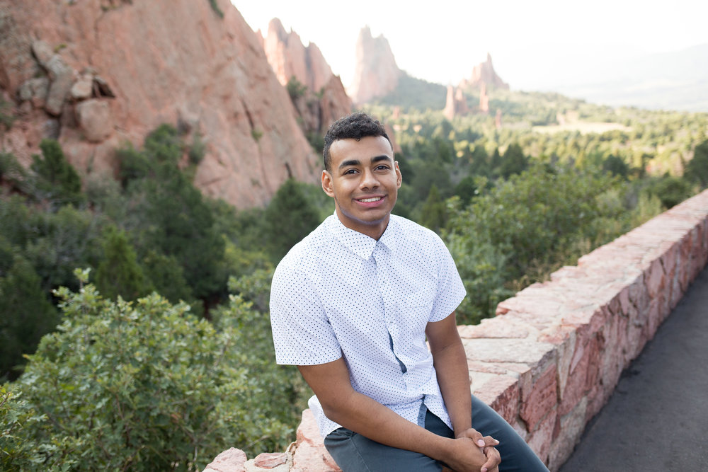 Headshot of Liberty High School senior smiling at the camera and sitting on  rock wall in Garden of the Gods, Stacy Carosa Photography, Colorado Springs Senior Portraits