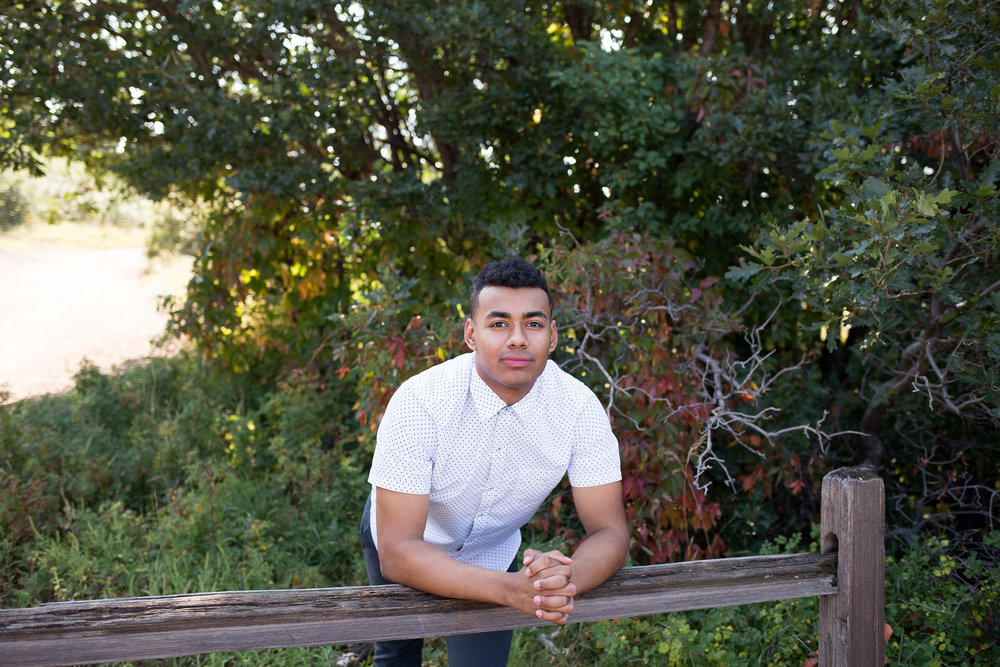 Male senior leaning on wooden fence with hands folded together smiling at the camera in Garden of the Gods,  Stacy Carosa Photogrpahy, Colorado Springs Seniors, Liberty High School