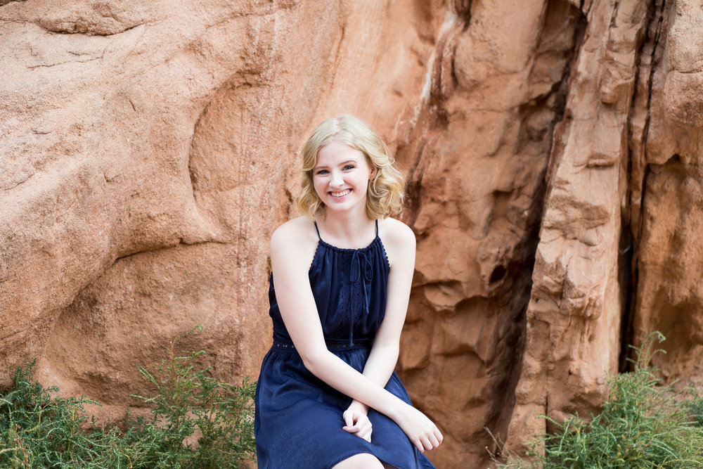 In Garden of the Gods for a senior session, girl sitting in front of red rock with arms crossed smiling, Stacy Carosa Photograpy, Colorado Springs
