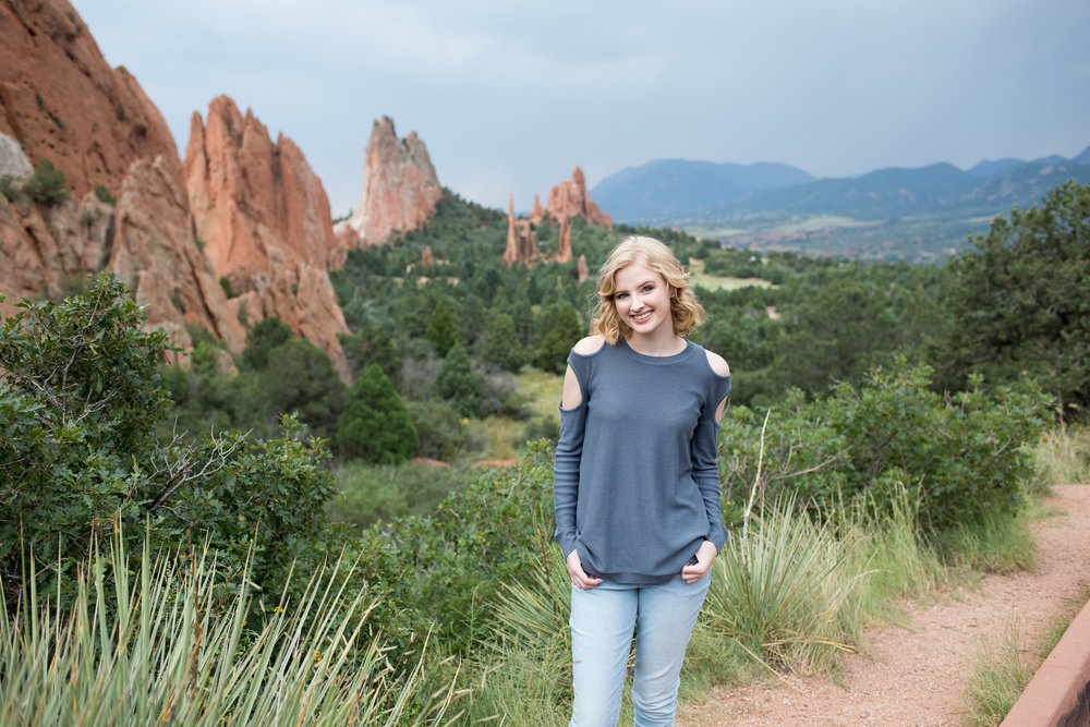 Beautiful Garden of the Gods backdrop for a senior session, girl with hands in pockets and green bushes around, Stacy Carosa Photography, Colorado Springs