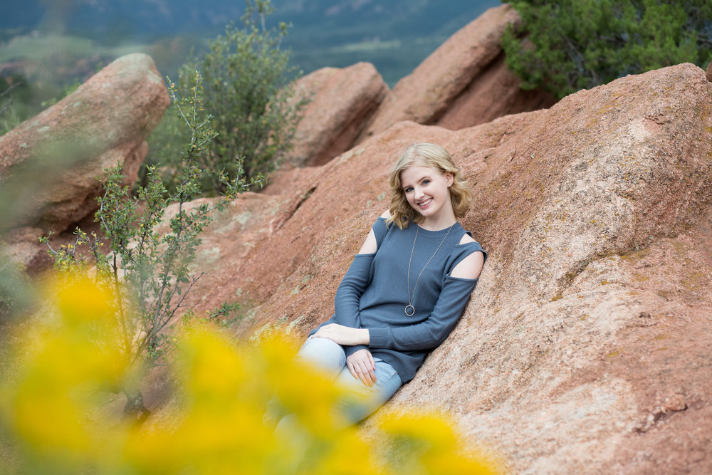 Yellow flowers in the foreground and senior girl leaning against red rock in Garden of the Gods park, Stacy Carosa Photography, Colorado Springs