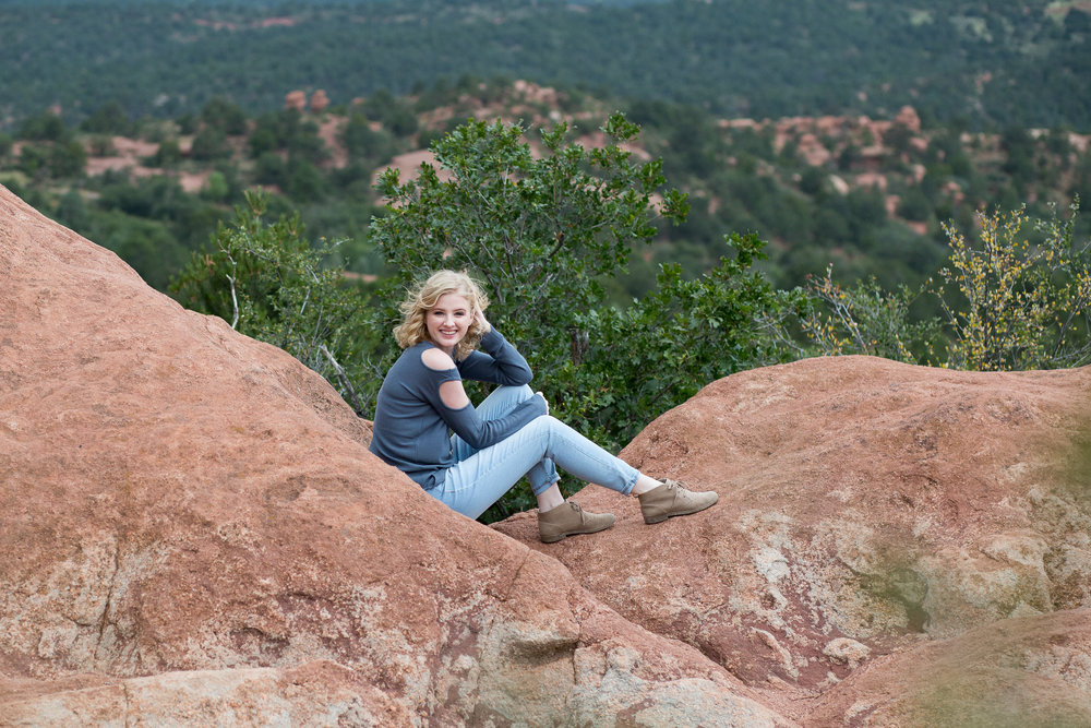 Girl leaning against red rock in Garden of the Gods with Manitou Springs in the background, Stacy Carosa Photography, Air Academy High School