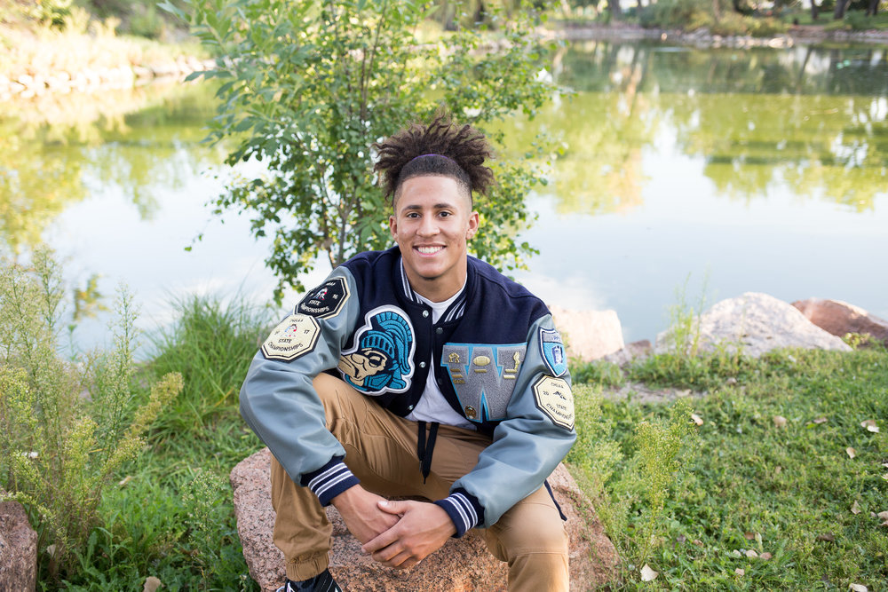 Senior from Widefield High  School sitting on rock at Monument Valley Park in Colorado Springs in his varsity jacket for his senior photo session, Stacy Carosa Photography