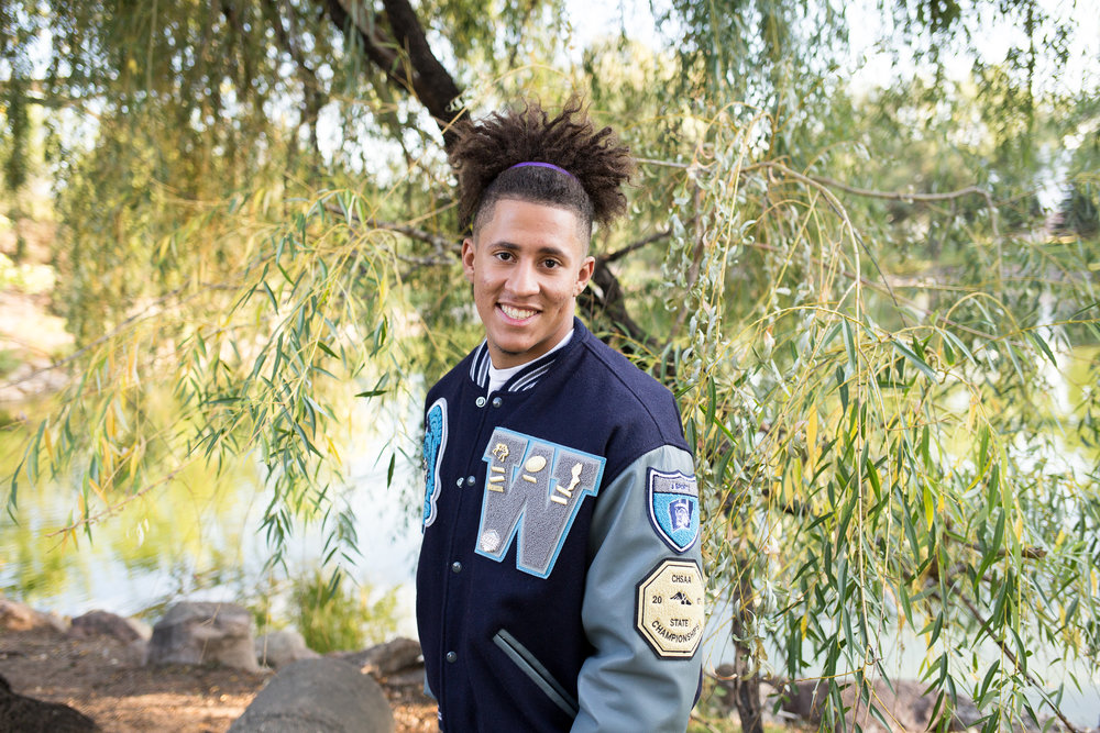 Male senior leaning toward camera in his varsity jacket smiling at camera. Widefield High  School Stacy Carosa Photography